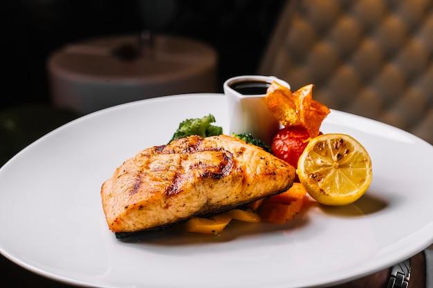 Vista frontal filete de pescado rojo a la parrilla con brócoli, una rodaja de tomate limón y salsa de narsharab