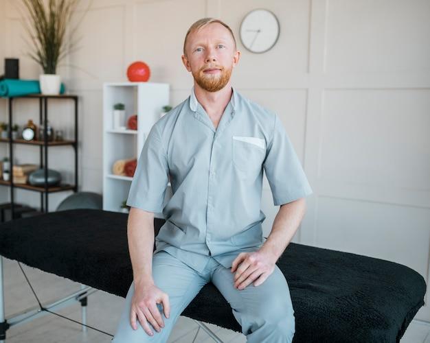 Vista frontal del fisioterapeuta masculino posando en la clínica