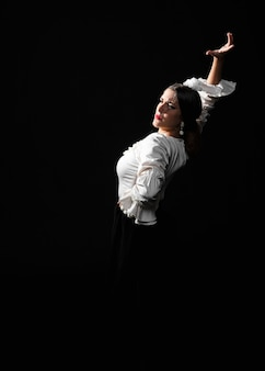 Vista frontal de flamenca bailando sobre un fondo negro