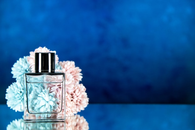 Vista frontal de las flores de la botella de perfume en el espacio libre de fondo borroso azul oscuro
