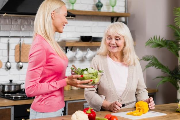Vista frontal foto de madre e hija sosteniendo una ensalada