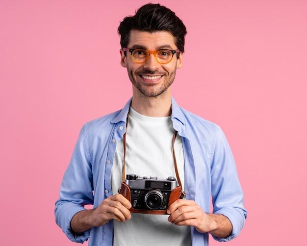 Vista frontal del fotógrafo masculino sonriente con cámara