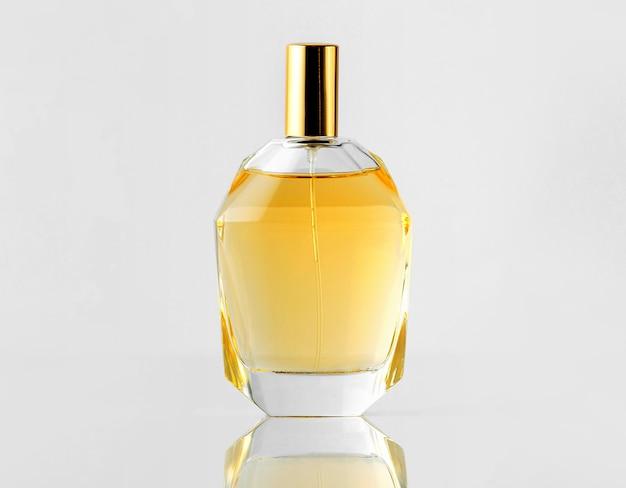 Una vista frontal de fragancia amarilla en botella con tapa dorada en la pared blanca