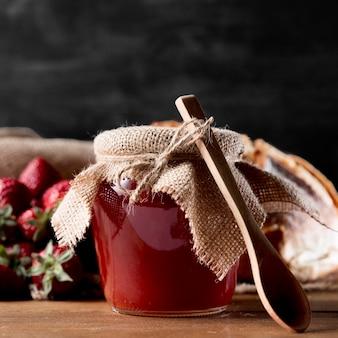 Vista frontal del frasco con mermelada de fresa