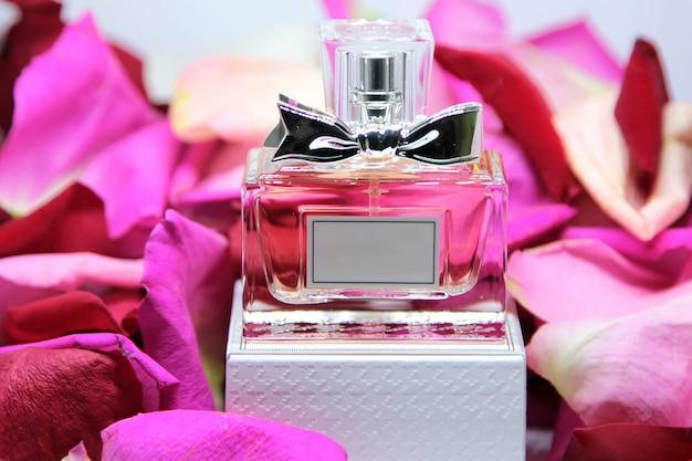Vista frontal frasco de perfume en caja con pétalos de rosa rosa