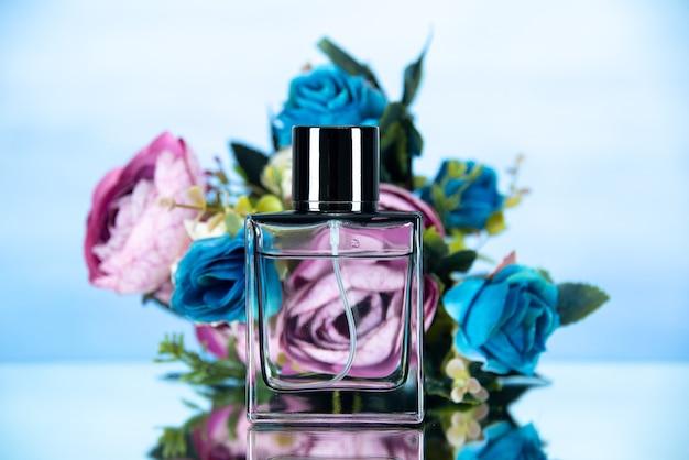 Vista frontal del frasco de perfume rectangular y flores de colores en la luz