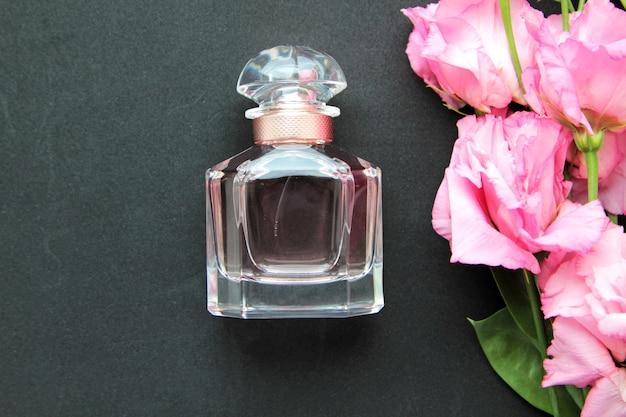 Vista frontal frasco de perfume con rosas rosadas