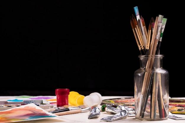 Vista frontal del frasco con pinceles y espacio de copia
