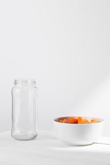 Vista frontal del frasco de vidrio con zanahorias baby para conservar