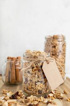Vista frontal de frascos con cereales para el desayuno y espacio de copia