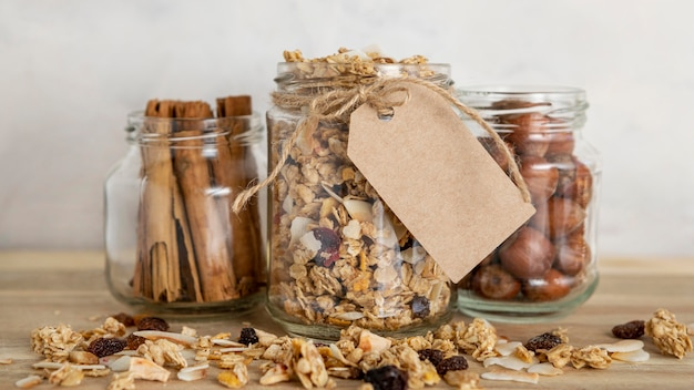 Vista frontal de frascos transparentes con cereales para el desayuno y etiqueta