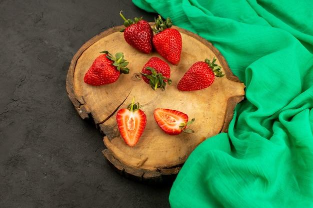 Vista frontal fresas frescas rojas maduras suaves en rodajas y todo en el escritorio de madera marrón sobre el gris