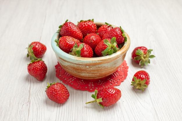 Vista frontal de fresas rojas en el escritorio blanco color rojo fruta baya fresca