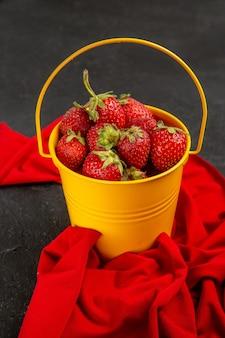 Vista frontal de fresas rojas frescas dentro de la canasta sobre el fondo oscuro