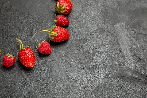 Vista frontal de fresas rojas frescas forradas sobre fondo gris oscuro