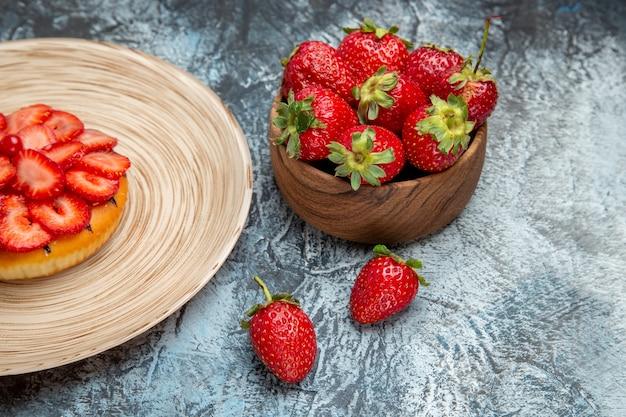 Vista frontal de fresas rojas frescas con panqueque en superficie clara