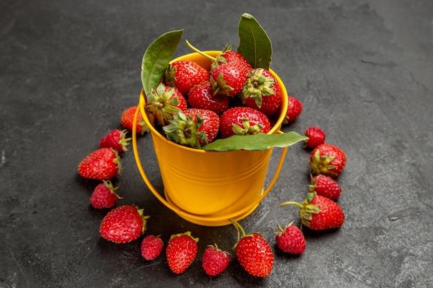 Vista frontal de fresas rojas frescas sobre el fondo oscuro