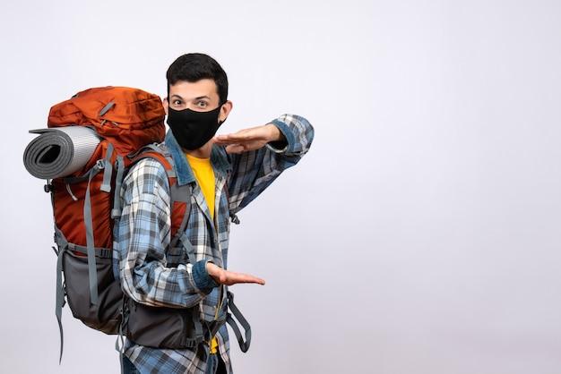 Vista frontal fresco joven excursionista con mochila y tamaño de siembra de máscara con las manos