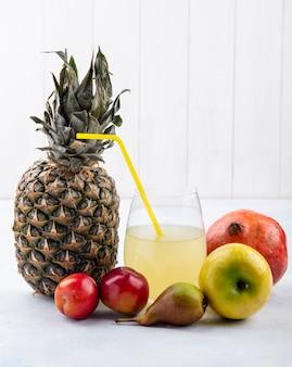 Vista frontal de frutas como piña ciruela manzana durazno y granada con jugo de piña en superficie blanca