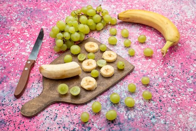 Vista frontal de frutas frescas en rodajas, uvas y plátanos en el escritorio púrpura color de jugo suave de frutas