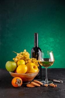 Vista frontal de frutas frescas en un tazón de manzana, membrillo, limón, uvas, caqui, botella de vino y galletas de vidrio, abridor de vino en la mesa verde