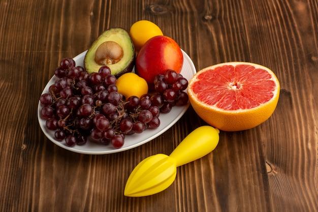 Vista frontal frutas frescas uvas mango aguacate y pomelo en escritorio marrón