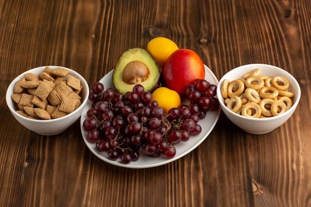 Vista frontal frutas frescas uvas mango aguacate y pomelo con galletas en el escritorio marrón