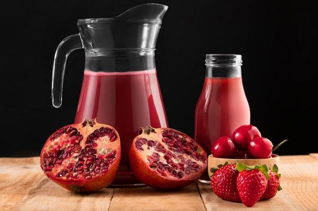 Vista frontal de frutas rojas y batido