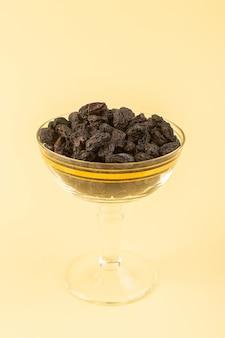 Una vista frontal frutas secas negras agrias secas dentro de un pequeño vidrio transparente aislado en el fondo de color crema fruta negra seca