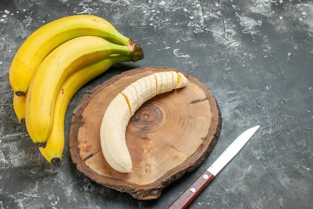 Vista frontal fuente de nutrición paquete de plátanos frescos y picados en un cuchillo de tabla de cortar de madera sobre fondo gris
