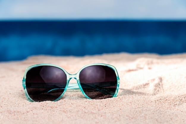 Vista frontal de gafas de sol en la arena de la playa