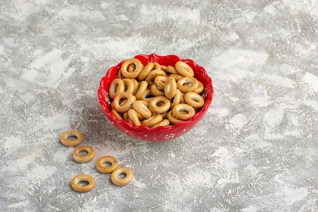 Vista frontal de galletas de anillo redondo dentro de la placa en el escritorio blanco