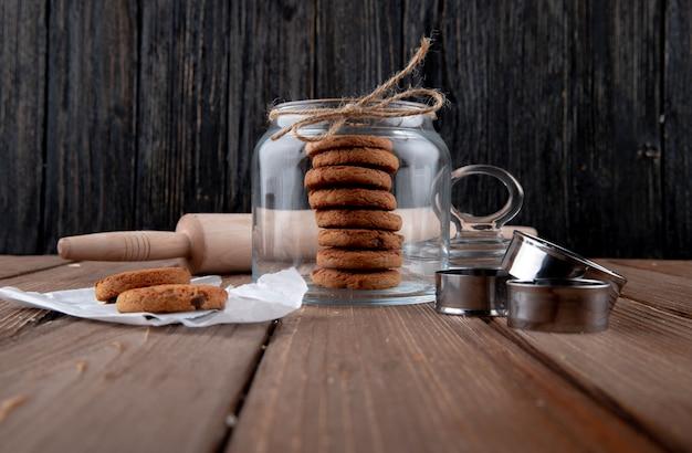 Vista frontal de galletas de avena en un frasco con un rodillo sobre la mesa