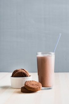 Vista frontal de galletas con chocolate con leche en vaso con paja