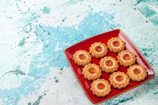 Vista frontal de galletas dulces con mermelada de naranja dentro de la placa roja sobre la superficie azul