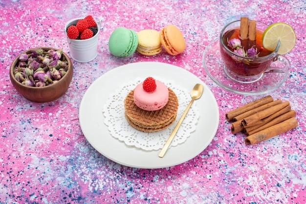 Vista frontal de galletas y macarons con té de canela en la superficie coloreada