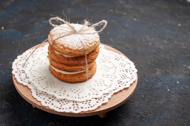 Vista frontal de las galletas sándwich con relleno de crema en la superficie oscura de la galleta de la galleta