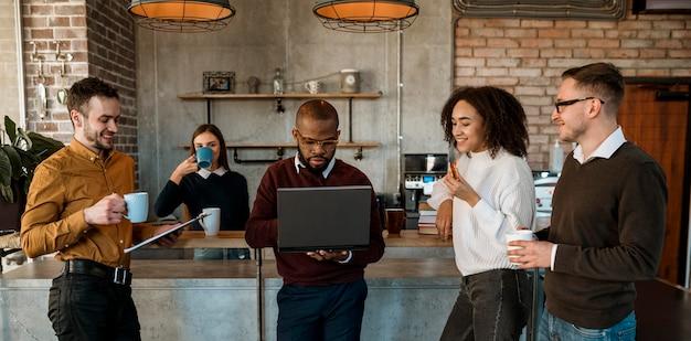 Vista frontal de la gente reunida con una taza de café