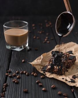 Vista frontal de glaseado de pastel y vaso de café