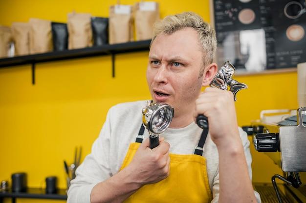 Vista frontal del gracioso barista posando mientras finge hablar por teléfono con herramientas