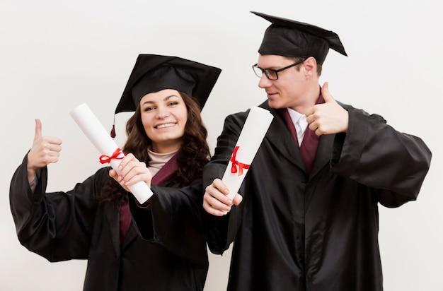 Vista frontal graduados dándose la mano