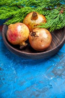 Vista frontal granadas frescas en tazón de madera rama de pino sobre fondo azul con espacio de copia