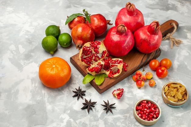 Vista frontal de granadas rojas frescas con mandarinas y ciruelas en el escritorio de color blanco claro
