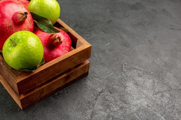 Vista frontal de granadas rojas frescas con manzanas verdes en el color de la fruta madura del piso oscuro