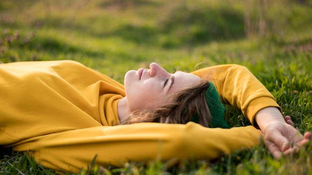 Vista frontal gratis chica quedándose en la hierba