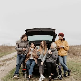 Vista frontal de un grupo de amigos en un viaje por carretera