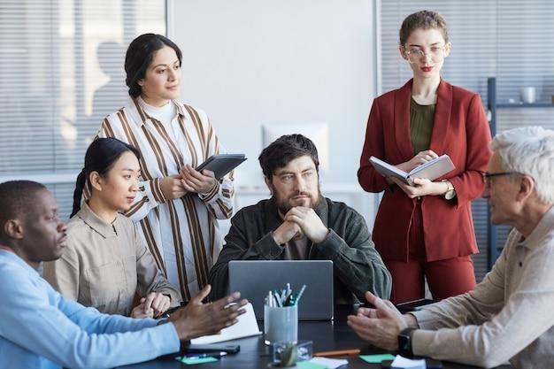 Vista frontal de un grupo diverso de empresarios que planifican un proyecto juntos mientras están sentados a la mesa durante una reunión en la oficina