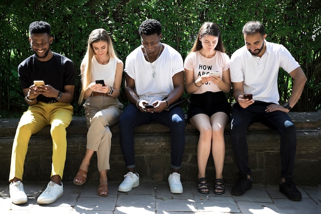 Vista frontal grupo diverso con teléfonos.