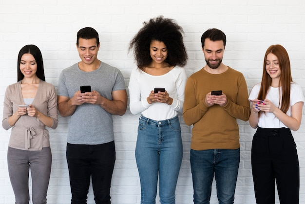 Vista frontal del grupo de personas enviando mensajes de texto en sus teléfonos móviles