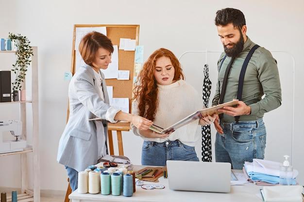 Vista frontal del grupo de tres diseñadores de moda que trabajan en atelier con paleta de colores